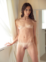 Magali playfully lifts up the hem of her dress until her humble yet delightfully puffy breasts and shaved pussy come into full view.
